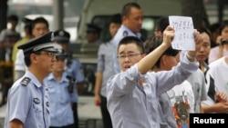 9月11日一名示威人士手舉紙張在日本駐北京大使館前抗議