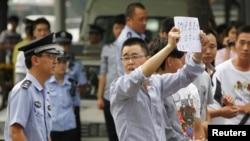 一名警察星期二在北京的日本大使館外對示威抗議者發話