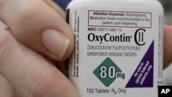 FILE - Pharmacist Steve Protzel holds a bottle of OxyContin in San Francisco, April 2, 2018.