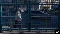 A man walks behind a locked passengers entrance of Athens' port of Piraeus which is on strike, May 6, 2016.