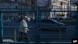 2016年5月6日,希臘一名男子走過一堵鐵攔,背後的雅典比雷埃夫斯港口工人正在參與罷工。