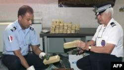 Des policiers retirent 38 kg de résine de cannabis ramenés d'Algérie, dans le réservoir aménagé d'un véhicule, à Lyon, le 18 juin 1999.
