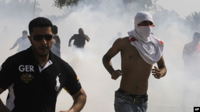 Anti-government protesters run away from tear-gas fired by riot police during a demonstration in Manama (file photo).