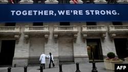 紐約證券交易所開市前,醫護人員抵達時用手肘相互致意。在關閉了兩個月之後,紐約證券交易所對交易員重新開放(2020年5月26日)。