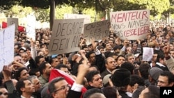 Tunisians shout slogans as they demonstrate against Tunisian President Zine al-Abidine Ben Ali in Tunis, 14 Jan 2011