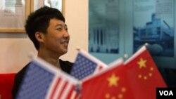 一位16歲的中國學生在北京一家教育機構裡的美中兩國國旗旁(2014年6月26日)