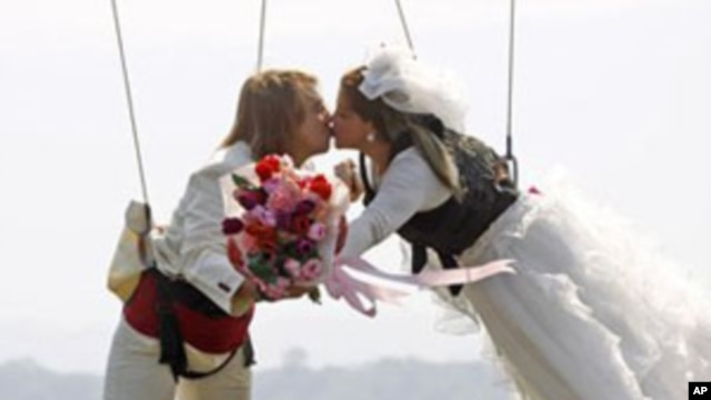 Thai-Swedish couple William Timhede, 23, left, and Napatsawan Timhede, 39, kiss as they hang on sling wireas part of an adventure-themed wedding ceremony in Thailand, on Monday, Feb. 13, 2012, on the eve of Valentine's Day.