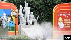 Xe quân đội phun khử khuẩn trên đường phố Hà Nội gần Hồ Hoàn Kiếm hôm 26/7. CDC khuyến cáo công dân Mỹ tránh du hành đến Việt Nam nếu không cần thiết.