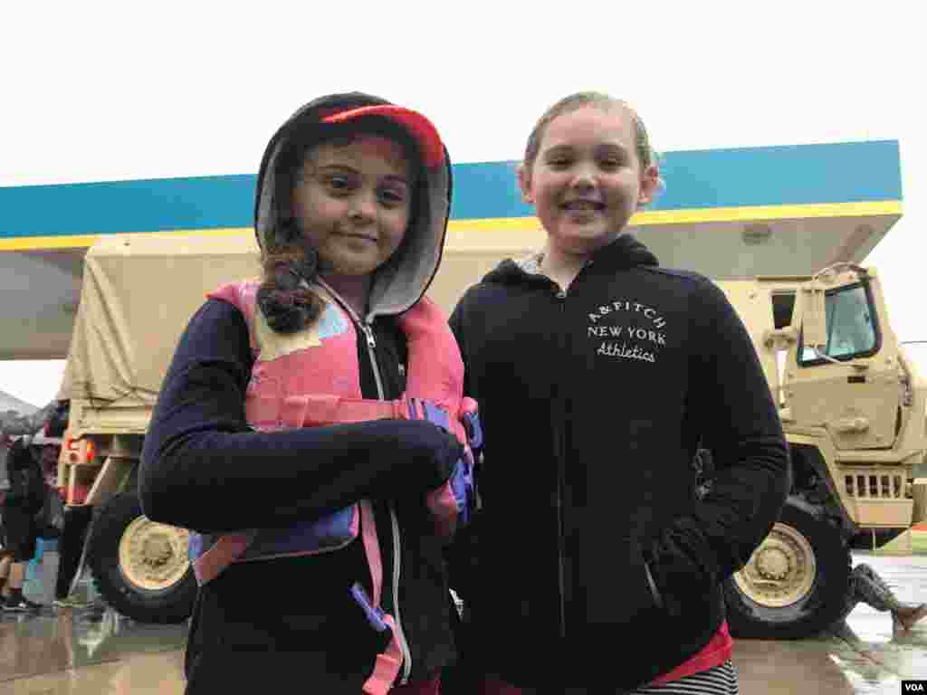 The Guel sisters – Sara, 7, at left, and Celeste, 8 – wait near the military transport truck that brought them from their flooded Greenbriar Colony neighborhood to a gas station transfer point in north Houston, Texas, Aug. 27, 2017. Next stop: a Red Cross