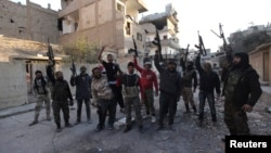 Members of the Jund Allah Brigades, part of the Free Syrian Army, hold their weapons as they pose for a photograph in Deir al-Zor, eastern Syria February 18, 2014.