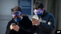 Travelers wear face masks and goggles as they use their smartphones outside the Beijing Railway Station in Beijing, Saturday, Feb. 15, 2020. (AP Photo/Mark Schiefelbein)