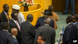 FILE - South Sudan's rebel leader Riek Machar, center-left with back to camera, shakes hands with South Sudan's President Salva Kiir, center-right wearing a black hat, after lengthy peace negotiations in Addis Ababa, Ethiopia, Aug. 17, 2015.