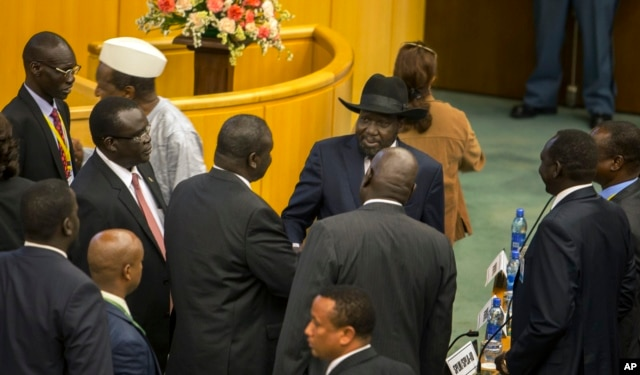 FILE - South Sudan's rebel leader Riek Machar, center-left, shakes hands with South Sudan's President Salva Kiir, center-right wearing a black hat, after lengthy peace negotiations in Addis Ababa, Ethiopia, Aug. 17, 2015.