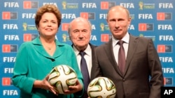 ARCHIVES - La présidente du Brésil Dilma Rousseff (gauche), le président de la Fifa Sepp Blatter (centre) et le président russe Vladmir Putin posent pour une photo lors de la cérémomie de la passation du flambeau à la Russie pour l'organisation du Mondial-2018