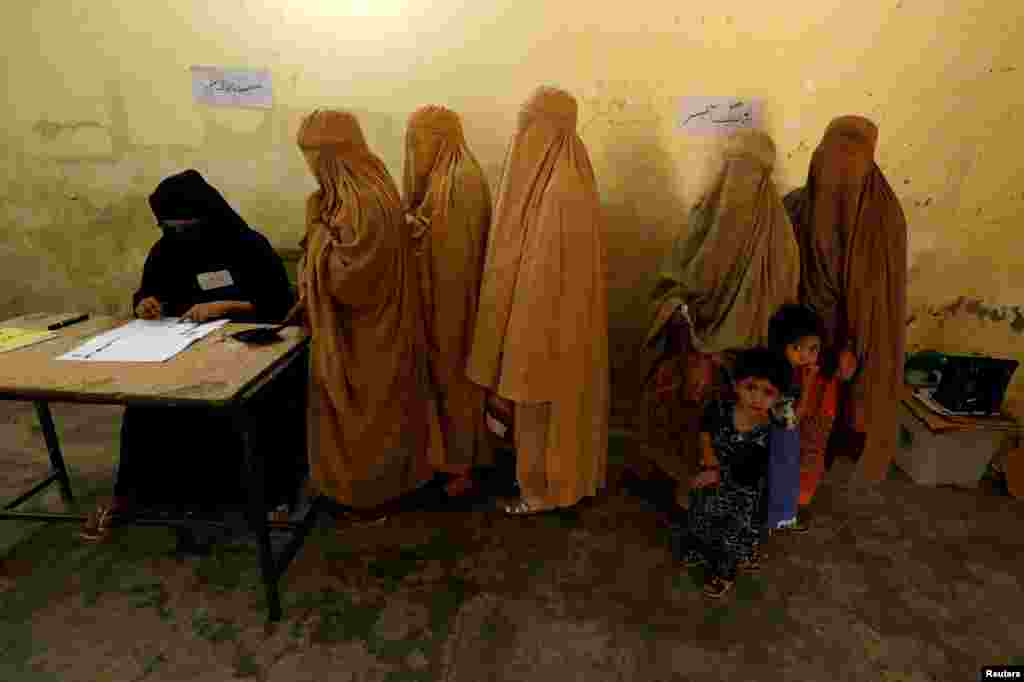 Women, clad in burqas, stand in line to cast their ballot at a polling station during general election in Peshawar, Pakistan.