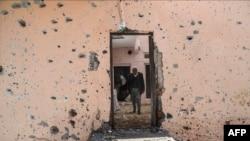 People walk inside their damaged house in the Sur district in Diyarbakir, Turkey, Dec. 11, 2015.