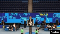 Serbia's Novak Djokovic and Taylor Fritz of the U.S. take a break during their third round match in Melbourne, Australia, Feb. 13, 2021