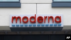 A sign marks an entrance to a Moderna, Inc., building, May 18, 2020, in Cambridge, Mass.