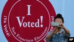 """Foto de mulher em frente a sinal """"Eu votei"""" em centro eleitoral em São Francisco"""