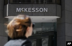 FILE - A pedestrian passes a McKesson sign on an office building in San Francisco, July 17, 2019.