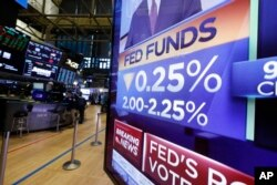 FILE - A television monitor on the floor of the New York Stock Exchange headlines a rate decision of the Federal Reserve, in New York, July 31, 2019.