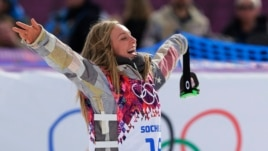 Jamie Anderson of the United States celebrates on the way to the flower ceremony after winning the women's snowboard slopestyle final at the 2014 Winter Olympics, Sunday, Feb. 9, 2014, in Krasnaya Polyana, Russia.