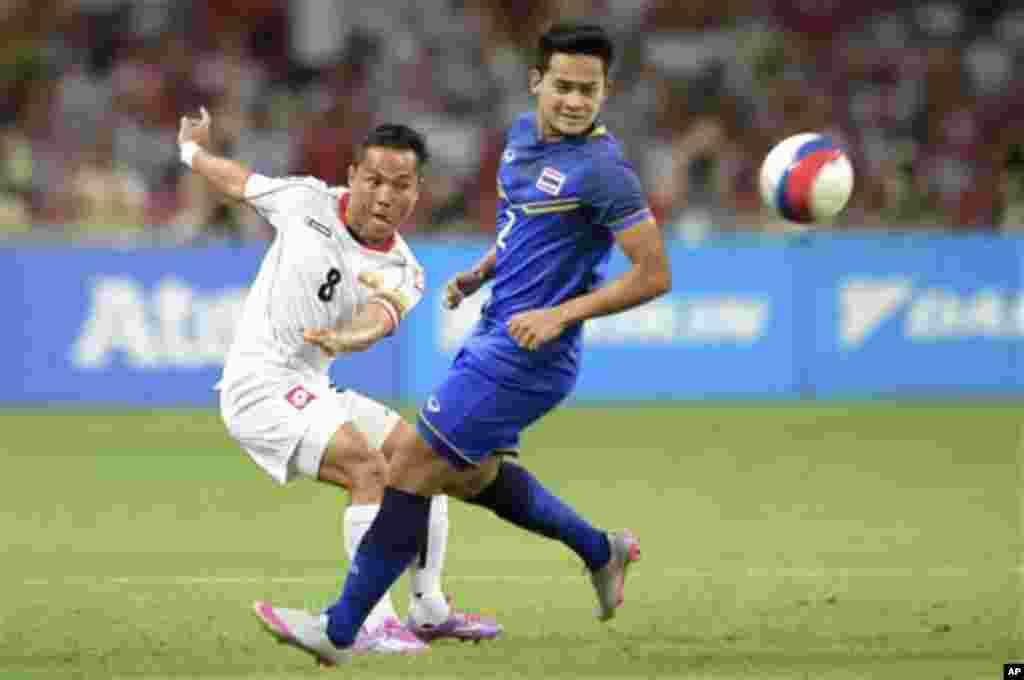 Nay Lin Tun of Myanmar, left, chips the ball past Peerapat Notechaiya of Thailand during the soccer final at the SEA Games in Singapore, Monday, June 15, 2015. (AP Photo/Joseph Nair)