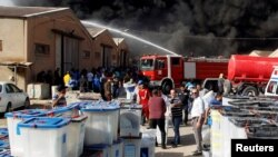 Smoke rises from a storage site in Baghdad, housing ballot boxes from Iraq's May parliamentary election, June 10, 2018.