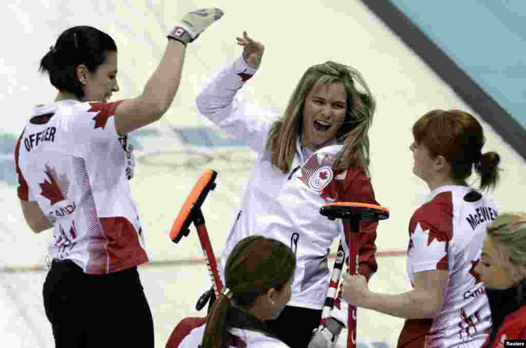 Canada's skip Jennifer Jones (center) celebrates with teammates Jill Officer (left) and lead Dawn McEwen after winning their women's curling semifinal game against Britain, Ice Cube Curling Center, Sochi Feb. 19, 2014.