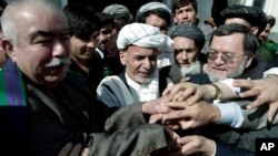 Ashraf Ghani, former Afghan finance minister, center, joins hands with his supporters after registering his candidacy in next year's presidential election, in Kabul, Afghanistan, Sunday, Oct. 6, 2013.