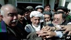 Ashraf Ghani, mantan menteri keuangan Afghanistan (tengah), berjabatan tangan dengan para pendukungnya. setelah mendaftarkan kepesertaannya dalam pemilihan presiden 2014 di Kabul (6/10).