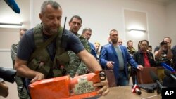 A pro-Russian fighter places a black box from the crashed Malaysia Airlines Flight 17 on a table while handing it over from Donetsk People's Republic officials to Malaysian representatives in the city of Donetsk, eastern Ukraine, July 22, 2014. Senior Ukrainian separatist leader Aleksander Boroda, (wearing a blue jacket) stands off to the right.