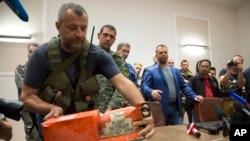 Ukraina sharqidagi isyonchilar Malayziya Havo Yo'llari vakiliga urib tushirilgan Boing samolyotidan topilgan qora qutini topshirmoqda, Donetsk, 22-iyul, 2014-yil