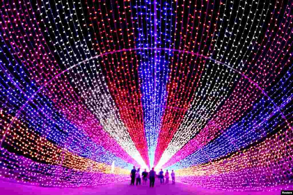 Para turis melewati karya seni 'instalasi lentera' di Zhangjiakou, Hebei, China.