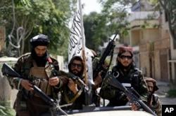 Kelompok Taliban mengibarkan bendera mereka saat berpatroli di Kabul, Afghanistan, 19 Agustus 2021. (Foto: AP)