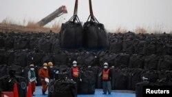 Công nhân di chuyển túi nhựa lớn màu đen có chứa bức xạ đất, lá cây và rác từ các hoạt động khử trùng tại khu vực lưu trữ tạm thời ở thị trấn Tomioka, tỉnh Fukushima.