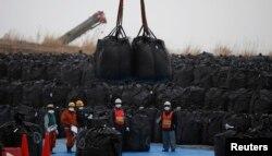 រូបឯកសារ៖ ក្រុមអ្នកជំនាញបច្ចេកទេសធ្វើការដឹកជញ្ជូនដីដែលមានសារធាតុវិទ្យុសកម្មដ៏គ្រោះថ្នាក់ នៅក្រុងTomioka តំបន់ Fukushima។