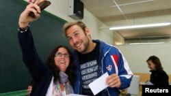 Pemilih di Barcelona, Spanyol mengambil foto selfie saat memilih (foto: ilustrasi). Sebagin besar negara bagian AS melarang foto selfie dari bilik suara pemilu.