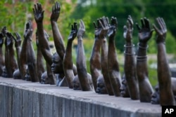 "This photo shows a bronze statue called ""Raise Up"", part of the display at the National Memorial for Peace and Justice, a new memorial to honor thousands of people killed in lynchings"