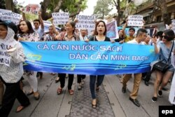 "FILE - Vietnamese protesters hold a banner reading ""Fish need clean water. People need the truth"" during a rally denouncing recent mass fish deaths in Vietnam's central province, in Hanoi, Vietnam, May 1, 2016."