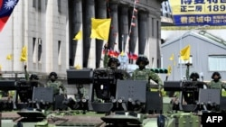 Taiwanese soldiers raise flags on military vehicles during a national day parade in front of the Presidential Palace in Taipei, Oct. 10, 2021.