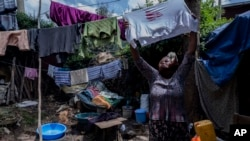Mother of two Amsale Hailemariam, a domestic worker who lost work because of the coronavirus, hangs clothes after washing them outside her small tent in the capital Addis Ababa, Ethiopia on Friday, June 26, 2020. (AP Photo/Mulugeta Ayene)