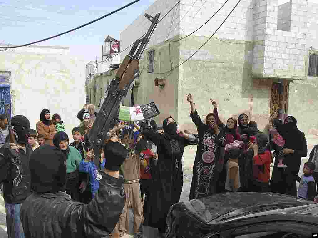 Syrians chant slogans against President Bashar Assad upon the arrival of the Free Syrian Army in a neighborhood in Damascus. (AP)