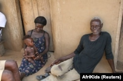 Angela, who was born in northern Ghana without lower legs, is pictured here as a baby with her mother and grandfather in northern Ghana, Oct. 2011.