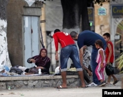 Algerian volunteers distribute free food for iftar (breaking fast) to Syrian refugee families who fled the violence in Port Said Square in Algiers, July 30, 2012.