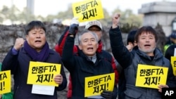 South Korean protesters from a farmers' group shout slogans during a rally denouncing the Free Trade Agreement (FTA) between South Korea and China in front of the National Assembly in Seoul, South Korea, Monday, Nov. 30, 2015.