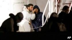 Dua penumpang yang selamat dari kapal migran yang terbalik di lepas pantai Libya menunggu di pelabuhan Catania, Italia, Senin (20/4).
