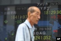 ຊາຍຄົນໜຶ່ງ ຍ່າງຜ່ານປ້າຍໄຟຟ້າ ສະແດງໃຫ້ເຫັນ ລາຄາຂອງຮຸ້ນ ຢູ່ໃນຕະຫຼາດ Nikkei ຂອງຍີ່ປຸ່ນ ທີ່ມີດັດສະນີຢູ່ 225 ທີ່ໄດ້ຕົກລົງ 80.18 ຄະແນນ ຫຼຶ 0.5 ເປີເຊັນ ສະເລ່ຍເປັນ 16,411.97 ຢູ່ທີ່ຕະຫຼາດຫລັກຊັບ ໃນໂຕກຽວ, ວັນທີ 21 ກັນຍາ 2016.