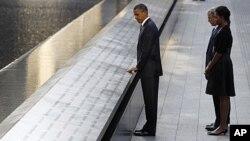 奥巴马总统周日抚摸着世贸中心北楼纪念水池护栏上刻着的遇难者的名字