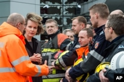 Belgium's Queen Mathilde, second left, visits firefighters and first responders in front of the damaged Zaventem Airport terminal in Brussels on March 23, 2016.